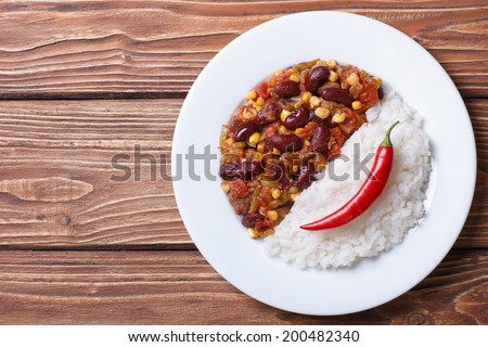 Tasty food: chili con carne and rice village background horizontal top view  - stock photo