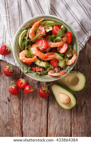 Tasty food: salad with shrimp, avocado and strawberry close-up on the table. Vertical view from above - stock photo