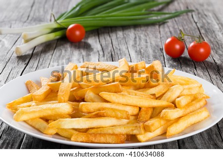 Tasty french fries on a white dish on wooden table background, close-up - stock photo