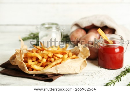 Tasty french fries on paper napkin, on wooden table background - stock photo