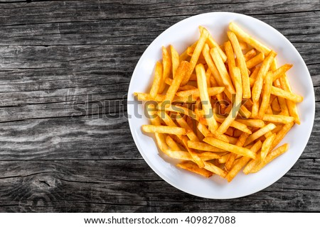 Tasty french fries on white plate, on wooden table background, blank space left, top view - stock photo