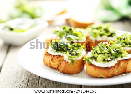 Tasty fresh bruschetta on plate on grey wooden background - stock photo
