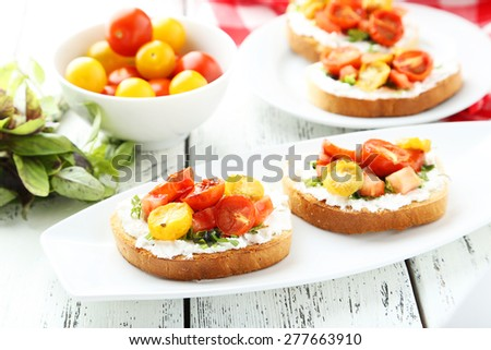 Tasty fresh bruschetta with tomatoes on plate on white wooden background - stock photo