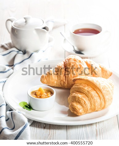 Tasty fresh croissants with jam and tea for breakfast