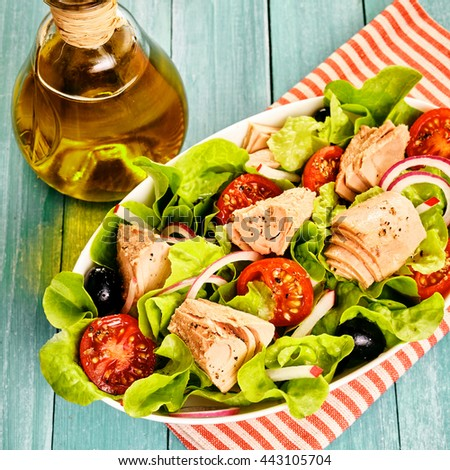 Tasty fresh Mediterranean tuna salad with mixed greens, onion, olives and tomato served in a bowl with olive oil dressing on a red and white striped napkin - stock photo