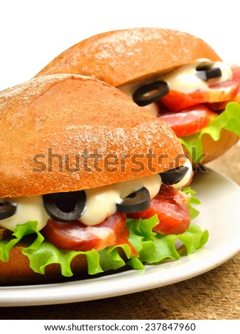 Tasty fresh sandwiches with green lettuce, ham and olives on white plate on sacking background, isolated on white - stock photo