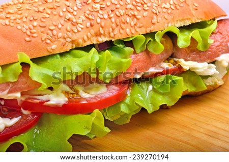 Tasty fresh sandwiches with green lettuce, sausages and tomatoes on wooden background