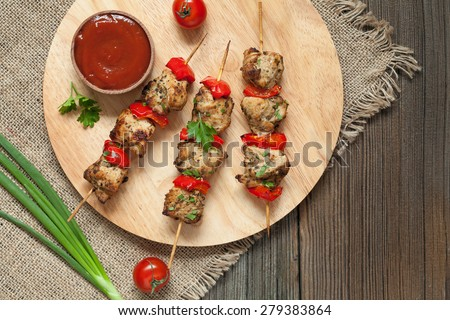 Tasty fried turkey or chicken kebab skewers bbq meat on wooden round desk with tomatoes, green onion, and sauce. Vintage textile and wooden background. Rustic style and natural light. - stock photo
