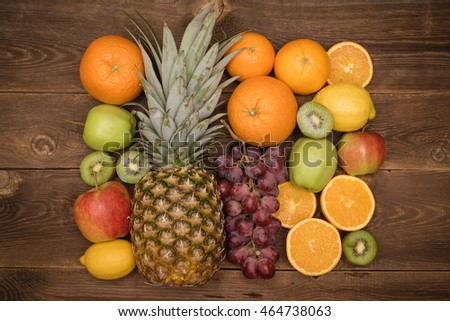 Tasty fruit background with orange, kiwi, grape, apples and lemon on the wooden table