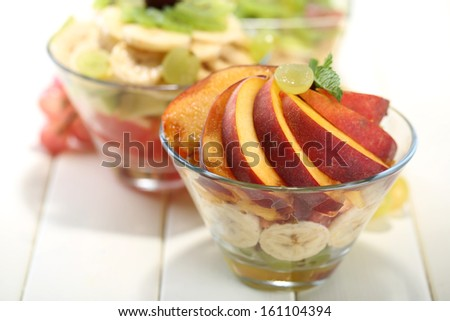 Tasty fruit salad in glass bowls, on white wooden table