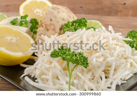 Tasty grated celery on a plate, on wooden background