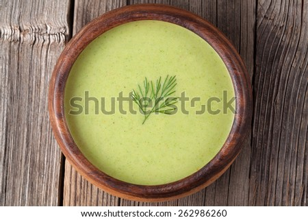 Tasty green cream vegetarian soup meal in wooden bowl on vintage table. Top view - stock photo