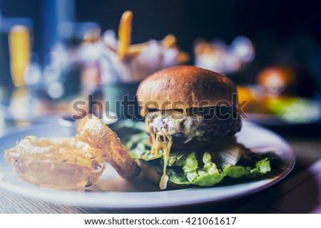 Tasty grilled beef burger with bacon and lettuce, mayonnaise served with french fries