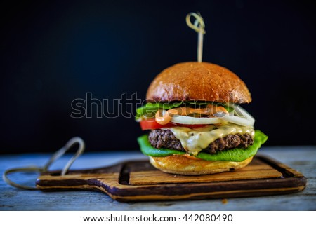 Tasty grilled beef burger with lettuce and mayonnaise served on wooden table with copyspace, blackboard in background.