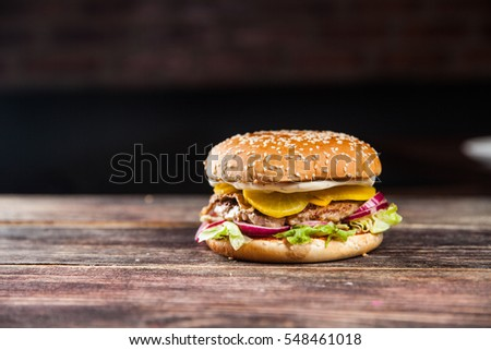 Tasty grilled beef burger with lettuce, ketchup, onion rings, chili and mayonnaise served on pieces of brown paper on a rustic wooden table of counter, with copyspace