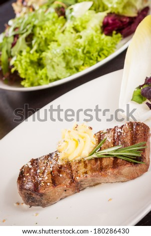 Tasty grilled beef steak topped with a twirled knob of butter and a sprig of fresh rosemary and served on a white plate, close up view