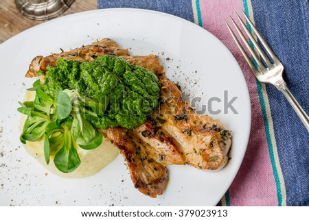 Tasty grilled chicken breast with pesto sauce and mashed potatoes on an old wooden table