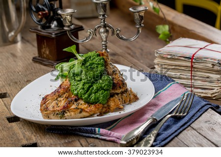 Tasty grilled chicken breast with pesto sauce and mashed potatoes on an old wooden table - stock photo