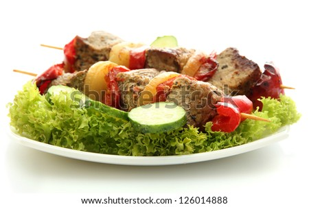 tasty grilled meat and vegetables on skewers on plate, isoalted on white - stock photo