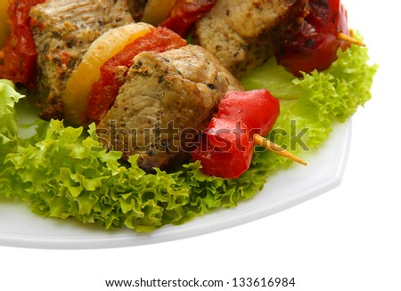 tasty grilled meat and vegetables on skewers on plate, isoalted on white