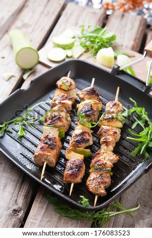 Tasty grilled meat on skewers in a grill pan