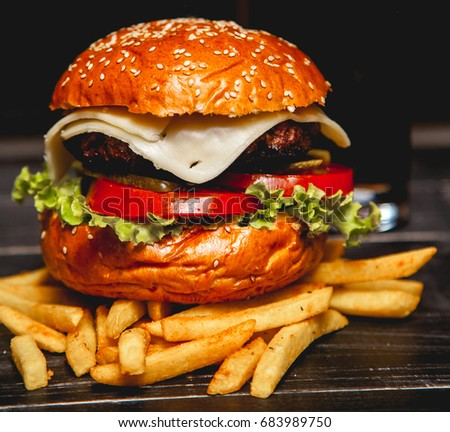 Tasty grilled prawn and beef burger with lettuce and mayonnaise served on wooden background. Top view
