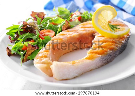 Tasty grilled salmon with salad on table close up - stock photo