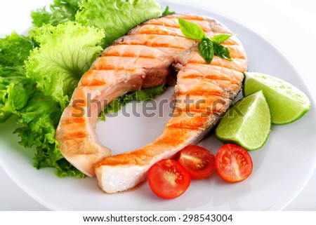 Tasty grilled salmon with tomato and lime on plate close up