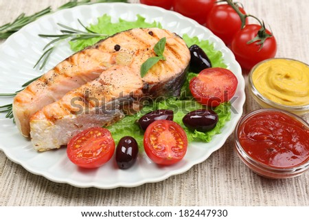Tasty grilled salmon with vegetables, close up - stock photo