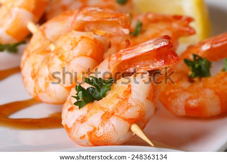 tasty grilled shrimp on wooden skewers macro with sauce on a plate. horizontal  - stock photo