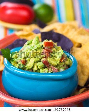 Tasty guacamole bowl with chips and fresh ingredients on the side. - stock photo