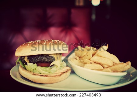 Tasty hamburger and french fries on plate in american food restaurant. Red leather sofa in the background. Vintage, retro style - stock photo