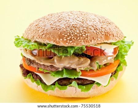 Tasty hamburger on yellow background. - stock photo