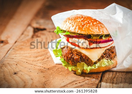 Tasty hamburger with fast food in a white paper on the wooden table. - stock photo