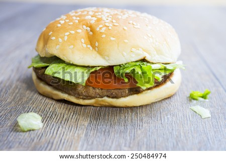 Tasty hamburger with meat, tomato and lettuce on wooden table  - stock photo