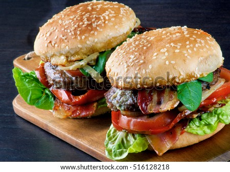 Tasty Hamburgers with Beef, Bacon, Lettuce, Tomatoes, Roasted Onion and Juicy Sauce on Sesame Buns on Wooden Cutting Board closeup on Dark background
