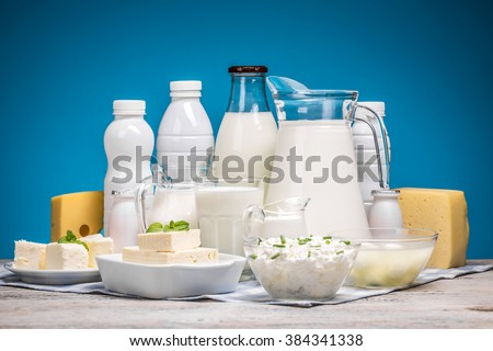 Tasty healthy dairy products on a table on a blue background - stock photo