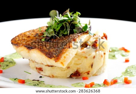 Tasty healthy fish fillet with potato puree with dried tomatoes and wild garlic sauce - stock photo