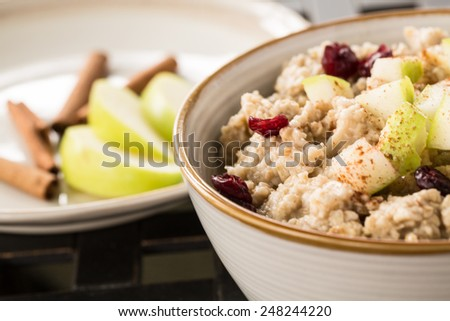 Tasty healthy oatmeal breakfast cereal with apples and cranberries and cinnamon sticks - stock photo