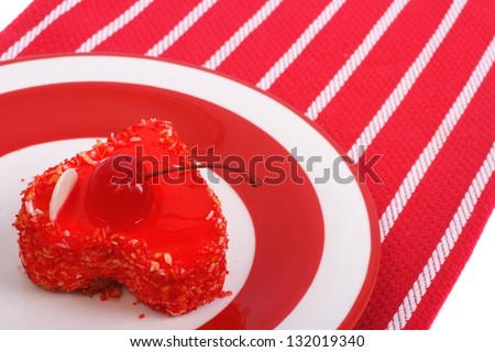 Tasty heart cake with a cherry close up on a red tablecloth with white stripes - stock photo