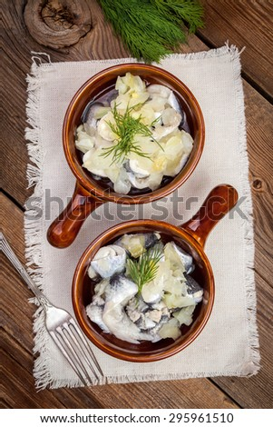 Tasty herring in pieces on a wooden table. - stock photo