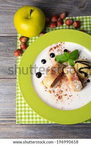 Tasty homemade apple strudel with nuts, mint leaves and ice-cream on plate, on wooden background - stock photo