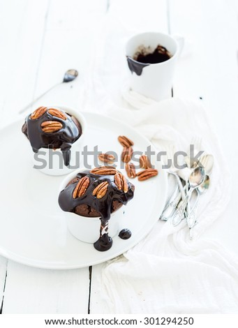 Tasty homemade brown muffins with chocolate ganache icing and pecan nuts in separate bakind cups, selective focus - stock photo