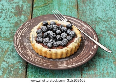 Tasty homemade cake with blackberries and icing sugar in brown plate on old turquoise table horizontal - stock photo
