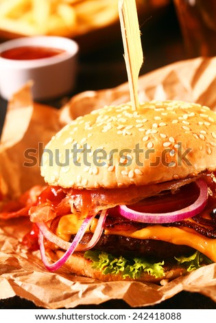 Tasty homemade cheeseburger on a sesame roll with a grilled beef patty, melted cheese and salad trimmings on crumpled brown paper - stock photo