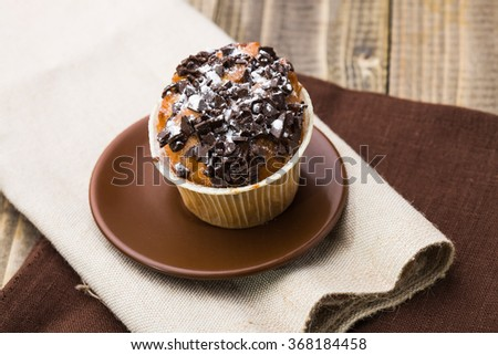Tasty homemade cupcake decorated by chocolate chips and powdered sugar on beautiful brown saucer standing on light and dark sackcloth fabric appetizing break time studio closeup top view, horizontal - stock photo