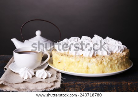 Tasty homemade meringue cake and cup of tea on wooden table, on grey background - stock photo