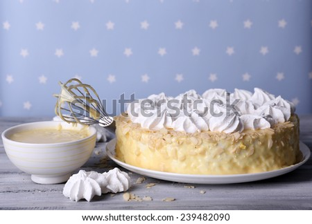 Tasty homemade meringue cake on wooden table, on blue background - stock photo
