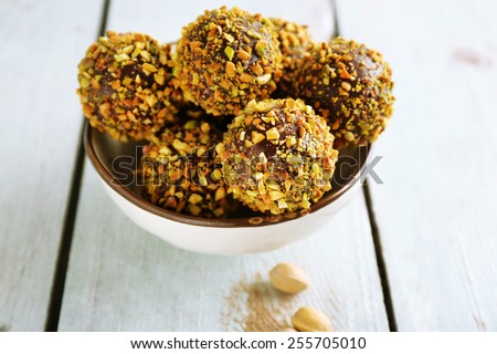 Tasty homemade pistachio candies on wooden table - stock photo