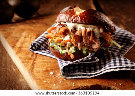 Tasty homemade pulled pork burger with fresh cucumber and mayonnaise trimming on a checkered cloth in a rustic kitchen - stock photo